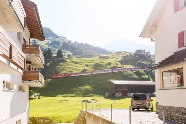 Hinten im Bild fährt ein Zug der Matterhorn Gotthard Bahn vom Oberalppass hinunter nach Andermatt.