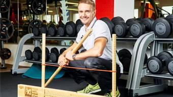 Sportwissenschafter Timon Baumgartner posiert mit dem Hilfsmittel «Functional movement screen» im Fitnesscenter «Vitasport Training». Bild: Colin Frei