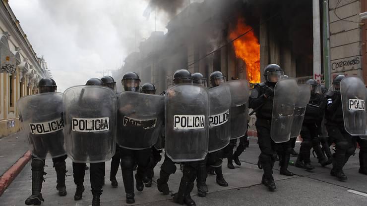 Polizisten bilden eine Blockade gegen Demonstranten. Bei Protesten gegen den Haushalt 2021 haben Demonstranten Teile des Kongresses in Brand gesteckt. Foto: Oliver De Ros/AP/dpa
