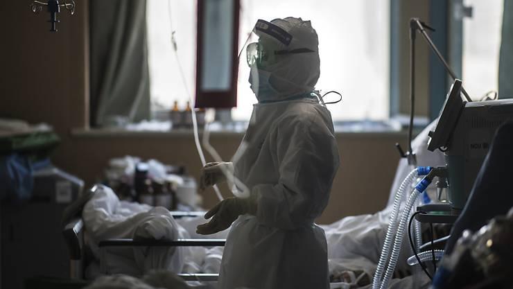 Eine Krankenschwester in Schutzkleidung betreut Patienten im Zentrum des Coronavirus-Ausbruchs in der Stadt Wuhan. (Foto: Xiao Yijiu/AP Keystone-SDA)
