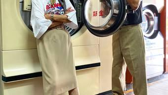 HANDOUT - Die 84 Jahre alte Hsu Hsiu-e und ihr 83 Jahre alter Mann Chang Wan-ji posieren in ihrer Wäscherei in Kleidung, die Kunden bei ihnen vergessen haben. Foto: Reef Chang/dpa - ACHTUNG: Nur zur redaktionellen Verwendung im Zusammenhang mit der aktuellen Berichterstattung und nur mit vollständiger Nennung des vorstehenden Credits