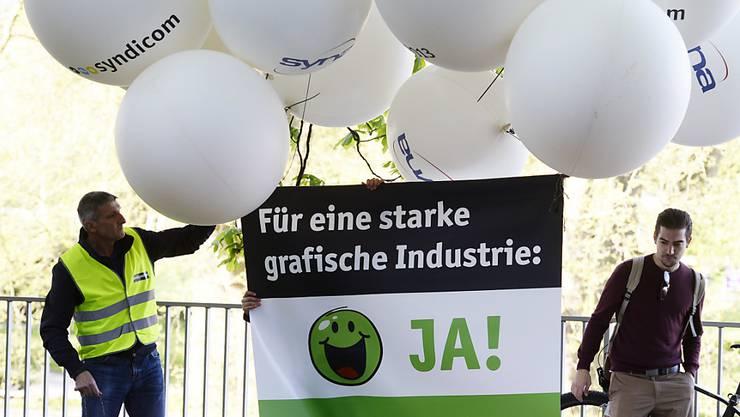Die grafische Industrie der Schweiz leidet weiterhin unter grossen strukturellen Veränderungen. Druckereiangestellte und Gewerkschaften forderten 2015 auf einem Transparent unter anderem Frühpensionierungen statt Entlassungen. (Archiv)