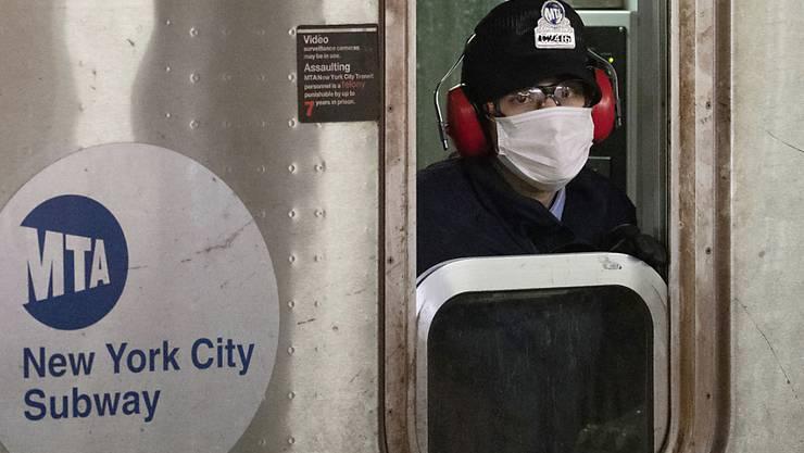 Weiterhin strenge Beschränkungen: Ein U-Bahn-Fahrer mit Schutzmaske in der Bronx in New York.
