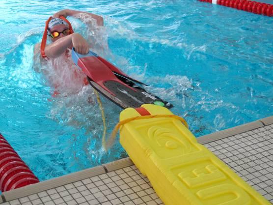 Schwimmer zieht sich bei der Wende die Flossen und Tube im Wasser an beim Super Lifesaver an.