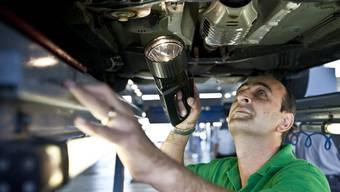Ein Verkehrsexperte prüft die Unterseite eines Fahrzeugs. (Symbolbild)