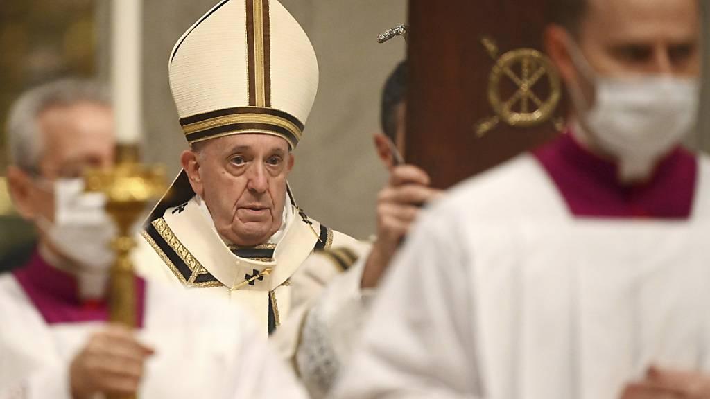 Papst Franziskus (m.) kommt in die Basilika Sankt Peter, um die Christmette zu feiern. Foto: Vincenzo Pinto/AFP POOL/AP/dpa