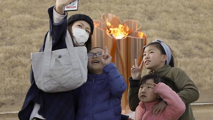 Eine Familie macht ein Selfie mit dem olympischen Feuer, das am Freitag in Japan eingetroffen ist