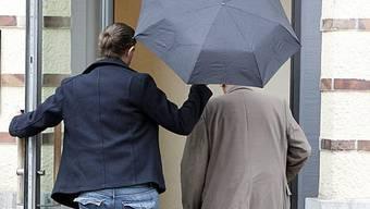 Einer der Angeklagten (rechts) wird in den Gerichtssaal gebracht