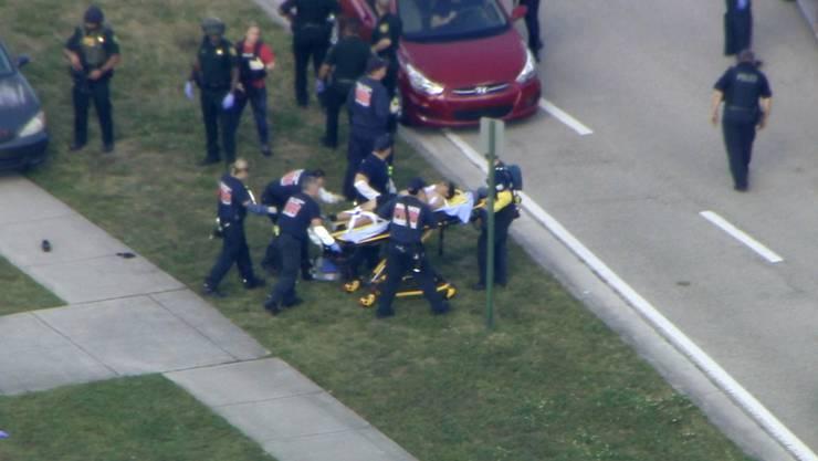 Einsatzkräfte kümmern sich um einen Verletzten vor der Schule in Parkland, US-Staat Florida.