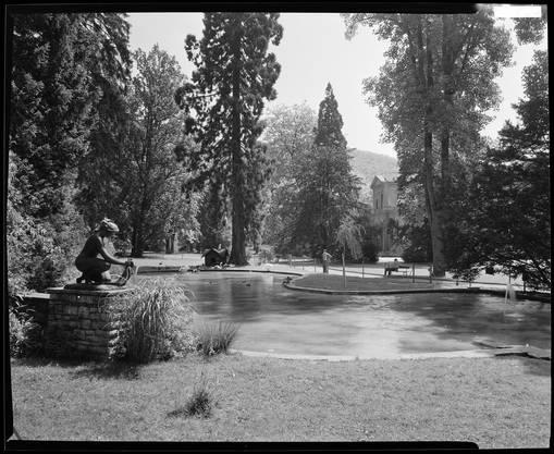 """Blick auf den Entenweiher im Kurpark mit Eduard Spörris Skulptur """"Badende"""" um 1947."""