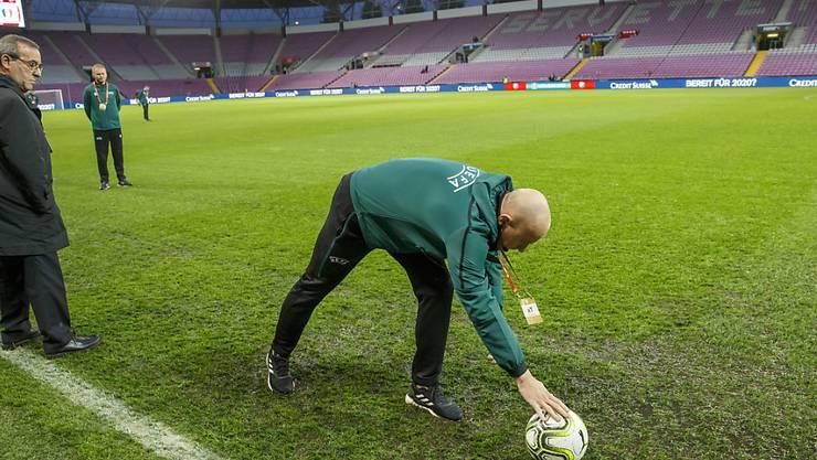 Schiedsrichter Szymon Marciniak inspiziert den durchnässten Platz im Stade de Genève und gibt grünes Licht für den Anpfiff um 20.45 Uhr