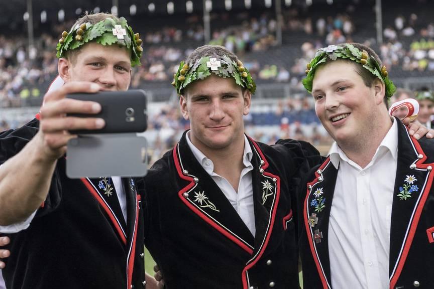 Der Bündner Armon Orlik posiert mit ebenfalls bekränzten Schwingkollegen zum Selfie am Eidgenössischen Schwing- und Älplerfest 2016 (KEYSTONE/Jean-Christophe Bott)