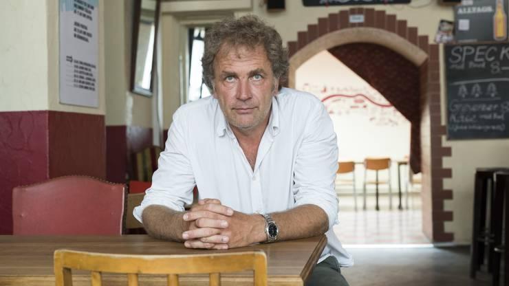 Alex Capus sitzt an einem Tisch in seiner Galicia Bar.