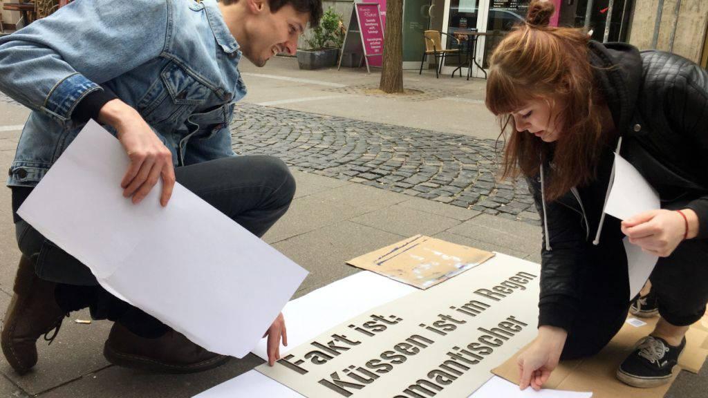 Kommunikationsdesign-Studenten legen in der Innenstadt von Mainz eine Schablone auf den Boden. Das Spray für die Aktion wird nur bei Kontakt mit Nässe sichtbar, also zum Beispiel wenn es regnet.
