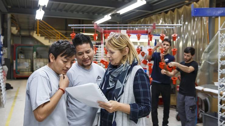 Romy Geiser im Gespräch mit zwei Flüchtlingen, die in den Werkhallen der Industrielackiererei in Derendingen arbeiten.