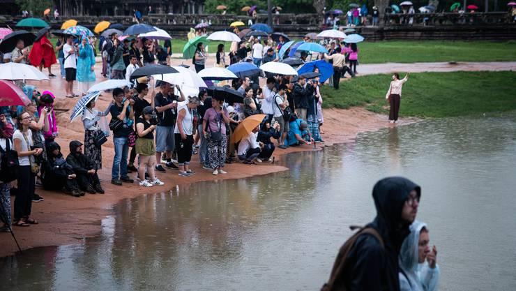Bereits am frühen Morgen und bei Regen warten viele Touristen vor dem bekannten Tempel Angkor Wat.
