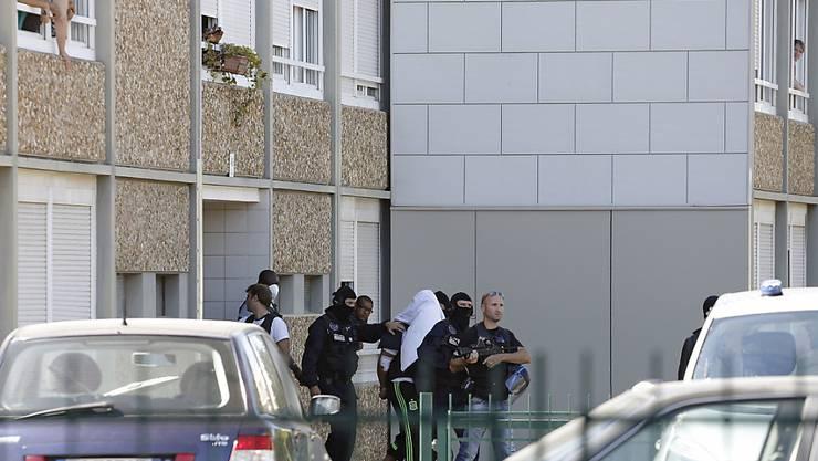Polizisten führen den Tatverdächtigen ab, der ein Tuch über dem Kopf hat (Archiv)