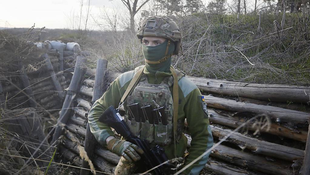 Ein bewaffneter ukrainischer Soldat trägt Militärkleidung und befindet sich in einer Kampfstellungen an der Trennlinie zum pro-russischen Separatistengebiet. Angesichts von Truppenaufmärschen auf russischem und ukrainischem Gebiet nahe dem Konfliktgebiet wächst die Sorge vor einer Eskalation.