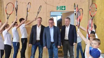 Vizeammann Luks Fässler, Tennisclub-Präsident Peter Lüscher und Landammann Alex Hürzeler (von links) betreten die Tennishalle. Die Tennisjugend steht Spalier.