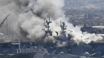 dpatopbilder - Rauch steigt vom US-Kriegsschiff «USS Bonhomme Richard» im Marinestützpunkt San Diego auf. Bei einem Feuer auf dem US-Kriegsschiff «Bonhomme Richard» in San Diego sind nach Angaben der Marine mehrere Soldaten leicht verletzt worden. Foto: Denis Poroy/AP/dpa