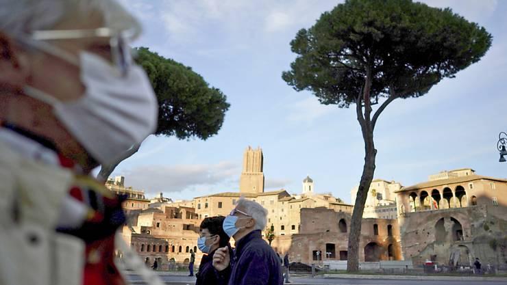 Passanten mit Mund-Nasen-Bedeckungen spazieren in Rom. Italiens Regierung hat die Schutzmaßnahmen während der Corona-Pandemie weiter verschärft. Foto: Andrew Medichini/AP/dpa