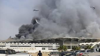 Löschhelikopter bekämpfen ein Feuer im neuen Bahnhof für Hochgeschwindigkeitszüge in der saudiarabische Stadt Dschidda.