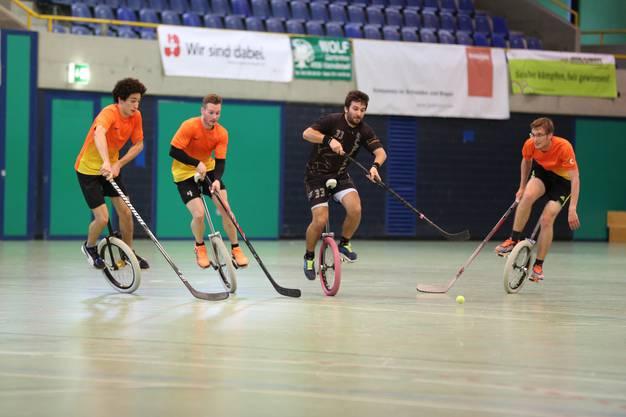Die Einradhockeyspieler aus Olten versuchen den Gegner am Schuss zu hindern.