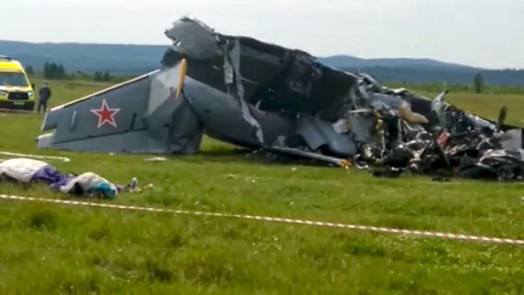 SCREENSHOT - Die Trümmer eines abgestürzten zweimotorigen Flugzeugs vom Typ L-410 liegen innerhalb eines abgesperrten Bereichs (bestmögliche Qualität). Beim Absturz eines Flugzeugs mit Fallschirmspringern an Bord sind heute in Sibirien in der Region Kemerowo mindestes vier Menschen ums Leben gekommen. Mehrere Menschen seien verletzt worden. Foto: Uncredited/RU-RTR Russian Television/AP/dpa