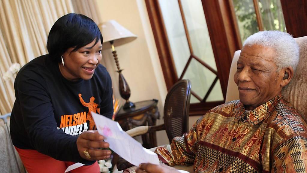 ARCHIV - HANDOUT - Nelson Mandela, 2013 verstorbener südafrikanischer Freiheitskämpfer, zeigt seiner jüngsten Tochter Zindzi Mandela einen Brief, in dem ihm zum 92. Geburtstag gratuliert wird. Zindziswa «Zindzi» Mandela ist tot. Foto: Debbie Yazbek/ Nelson Mandela Fo/NELSON MANDELA FOUNDATION/dpa