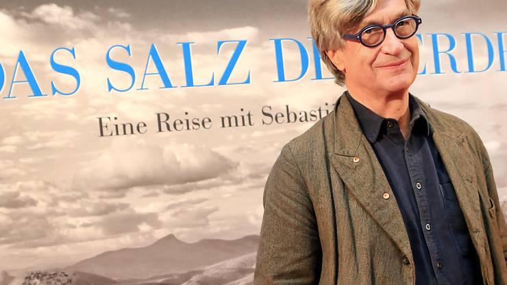 """ARCHIV - Der Regisseur Wim Wenders steht bei der Premiere des Films """"Das Salz der Erde"""" in der Lichtburg vor dem Filmplakat in Essen. Foto: Marcel Kusch/dpa"""