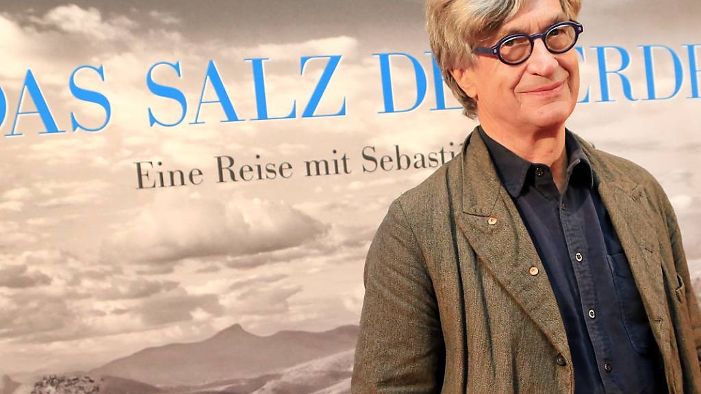 ARCHIV - Der Regisseur Wim Wenders steht bei der Premiere des Films «Das Salz der Erde» in der Lichtburg vor dem Filmplakat in Essen. Foto: Marcel Kusch/dpa