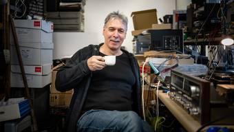 Max Aeschlimann arbeitet in einem Raum voller zu reparierender Geräte.