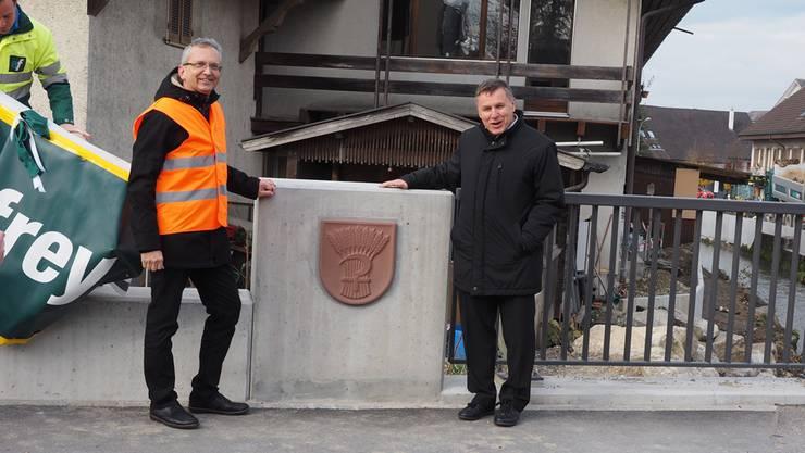 Gemeindeammann Fredy Böni (r.) und Peter Keller vom Kanton enthüllen das Wappen an der neuen Möhlinbachbrücke. twe