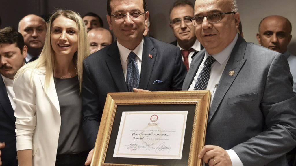 Der neue Bürgermeister von Istanbul, Ekrem Imamoglu (Mitte), präsentiert seine Ernennungsurkunde.