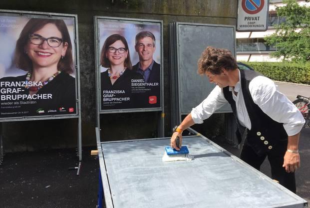Ein Helfer der SP Aarau trägt den Kleber auf die Plakate auf