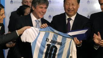 Chinas Präsident Xi Jinping (rechts) erhält ein Fussballtrikot