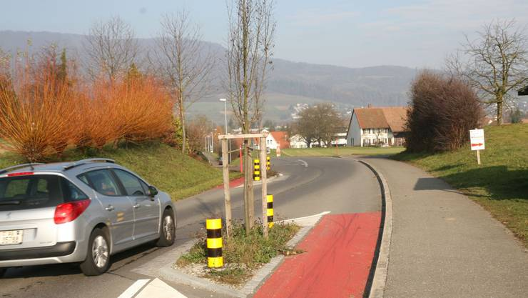 Ein Auto kommt bei der Verengung gut durch. Die Velofahrer können auf dem rot bemalten Streifen fahren.  barbara vogt