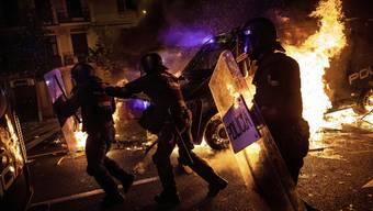 Polizisten zwischen brennenden Barikaden.