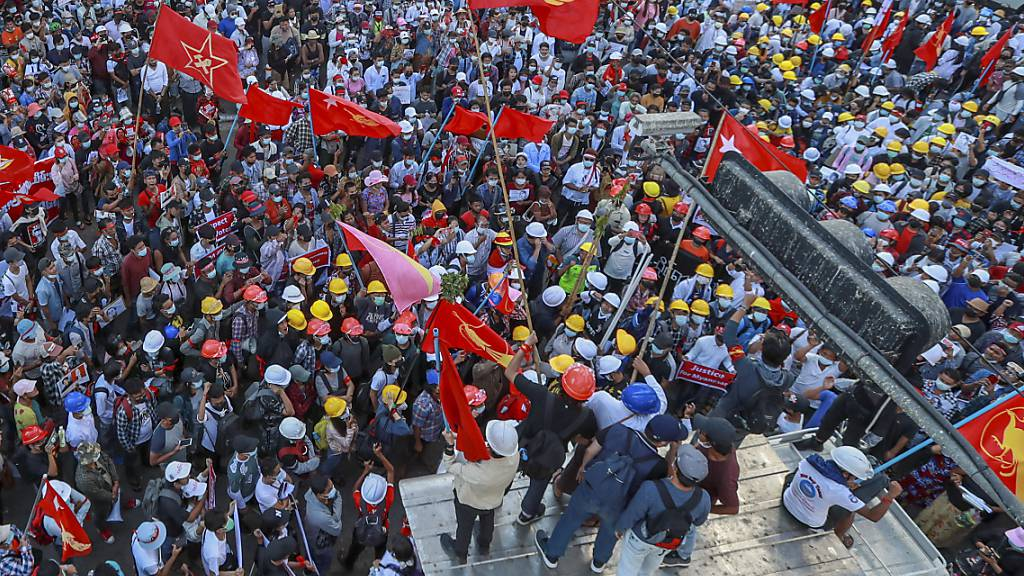 ARCHIV - Demonstranten schwenken Fahnen der Partei National League for Democracy während eines Protestes gegen den Militärputsch in Myanmar. Foto: Uncredited/AP/dpa