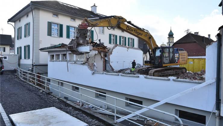 Mit schwerem Gerät rückt eine spezialisierte Firma dem Primarschulhaus zu Leibe. Das alte Schulhaus im Hintergrund wird saniert.