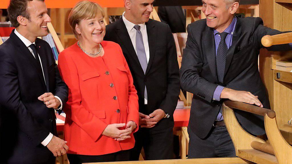 Frankreichs Präsident Emmanuel Macron, Bundeskanzlerin Angela Merkel und Bundesrat Alain Berset (von links) lassen sich an der Eröffnung der Buchmesse in Frankfurt erklären, wie die Gutenberg-Buchpresse funktionierte.