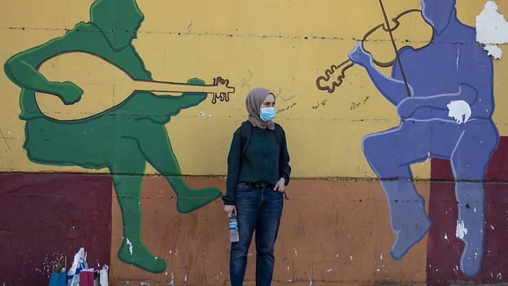 Eine Frau mit Mundschutz wartet vor einer Wand, auf das ein musikalisches Graffiti gemalt ist, auf den Bus. Wenige Tage vor einem Lockdown ist in Israel die Zahl der täglichen Corona-Neuinfektionen erneut auf einen Rekordwert gestiegen. Foto: Ariel Schalit/AP/dpa
