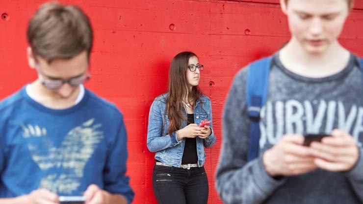 Jugendliche am Handy; einen grossen Teil ihrer Freizeit investieren sie in soziale Medien. Keystone