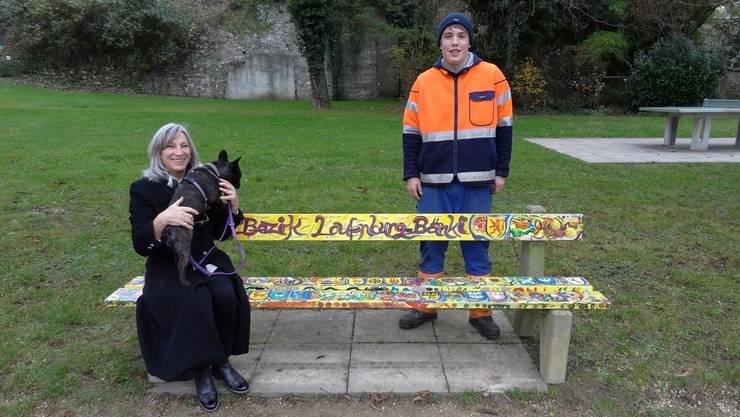 Lisa Brutschi posiert zusammen mit Hund und Betriebspraktiker-Lehrling Tim Brogli. Er hat das Bänkli soeben montiert.