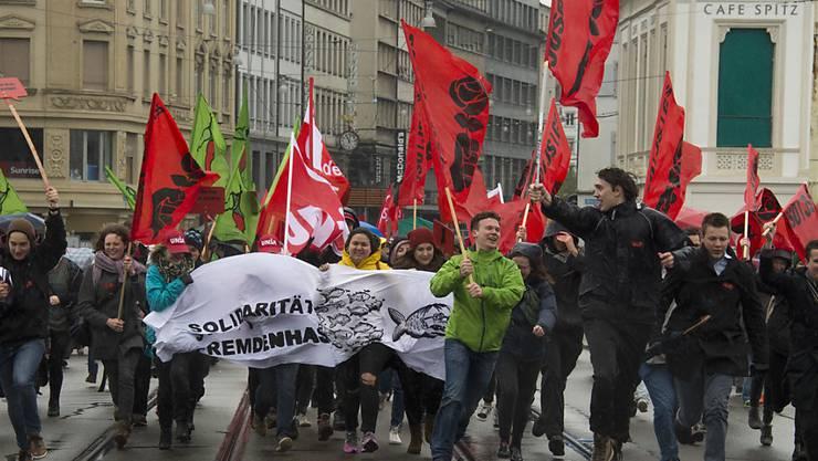 Kundgebungsteilnehmer rennen mit Transparenten und Fahnen am traditionellen 1. Mai-Umzug am Tag der Arbeit.