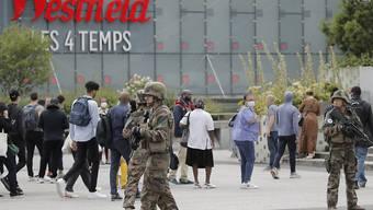 """Soldaten patrouillieren vor dem Einkaufszentrum """"Les Quatre Temps"""" im Geschäftsviertel La Défense westlich von Paris. Foto: Christophe Ena/AP/dpa"""