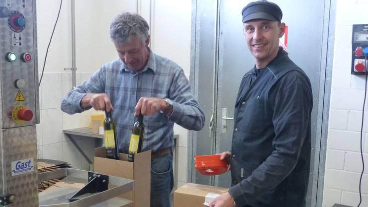 Weinbauer Emil Hartmann (links) und Schwiegersohn Pascal Furer packen die frisch etikettierten Flaschen ab.