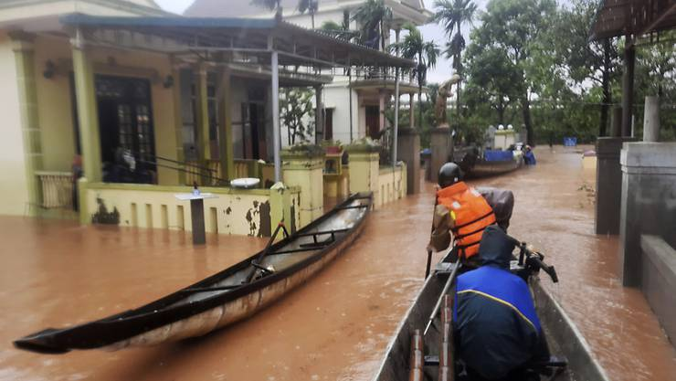 Rettungskräfte fahren mit einem Boot durch ein überflutetes Dorf. Bei anhaltendem Regen und schweren Überflutungen in Vietnam sind bis zum Montag mindestens 18 Menschen ums Leben gekommen. Foto: Ho Cau/VNA/AP/dpa