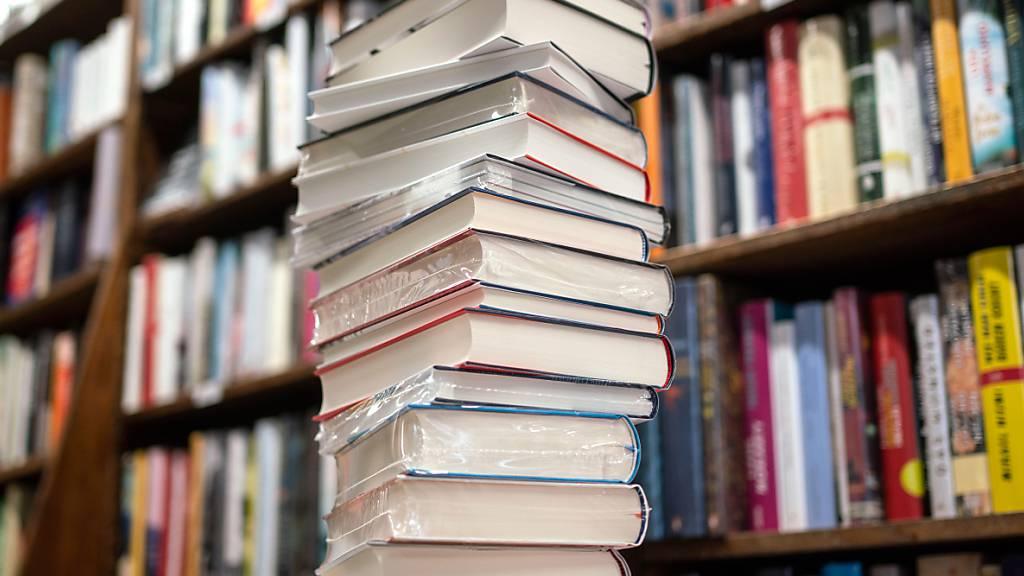 ARCHIV - Ein Stapel neuer Bücher liegt auf einem Verkaufstisch in einer Buchhandlung im Stadtteil Bornheim. Was sind die preisverdächtigsten Romane des Jahres? Der Börsenverein des Deutschen Buchhandels hat die sogenannte Longlist für den Deutschen Buchpreis 2021 bekanntgegeben. Foto: Frank Rumpenhorst/dpa/Frank Rumpenhorstdpa