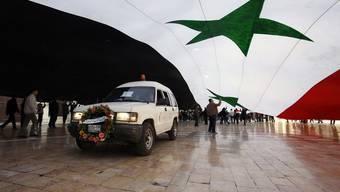 Trauerzug unter einer gigantischen syrischen Flagge